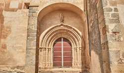Porch of an old Catholic chapel located in Spain, with wooden door and facade of carved stone and adobe