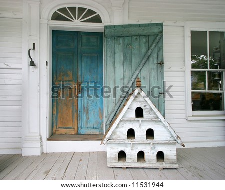 porch on antique building with large birdhouse