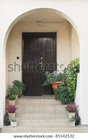 Porch with a wooden dark brown door and flowers