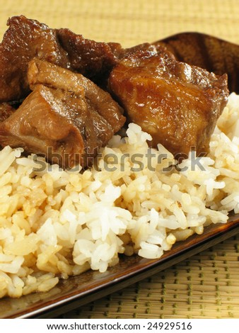 Pork adobo prepared in soy sauce, vinegar, and spices.