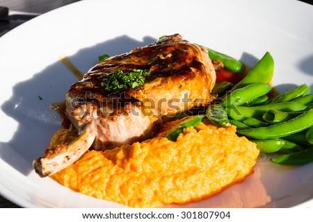 pork chop dinner outdoors under a warm romantic afternoon light