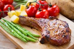 pork chop serve with vegetable on wooden board