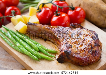 Photo of  pork chop serve with vegetable on wooden board