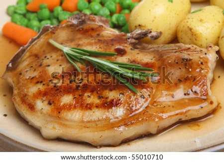 Pork chop with new potatoes, vegetables and gravy.