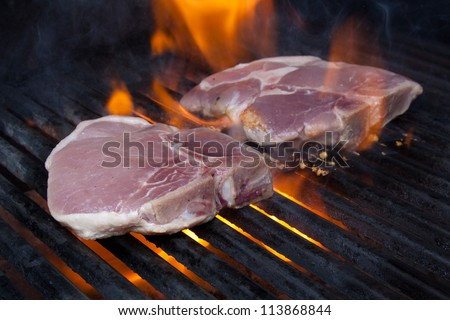 Pork Chops on Grill with Flames - stock photo