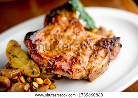 Photo of  Pork chops. Pork chops seasoned with cracked black pepper and grilled. Pork served with classic steakhouse side dishes: asparagus and mashed potatoes. Classic fine dining entree.