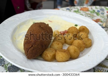 Pork cutlet and potatoes served on plate in restaurant