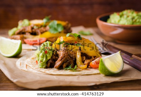 Shutterstock Pork fajitas with onions and colored pepper, served with tortillas and guacamole