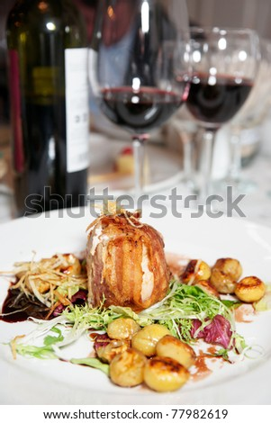 Pork grilled with bacon and chestnuts on a plate
