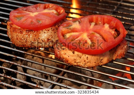 Pork Loin Pepper Steaks On The Hot BBQ Grill With Vibrant Flames In The Background, Close Up