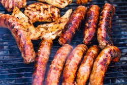 Pork meat and sausages grilled on a charcoal barbeque. Top view of tasty barbecue, food concept, food on grill and detail of food on the grill