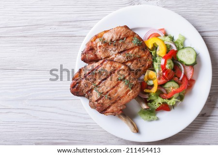 Pork meat grilled with fresh vegetable salad on a white plate. a top view of a horizontal  #211454413
