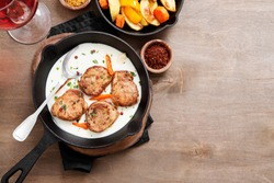 Pork meat medallions with baked potatoes and cream sauce .
