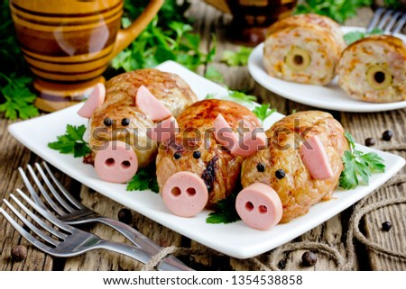 Pork meatballs - baked cutlet meatball meatloaf stuffed with minced meat and rice in crispy chicken skin shaped funny pigs with sausage snout and ears and black pepper eyes