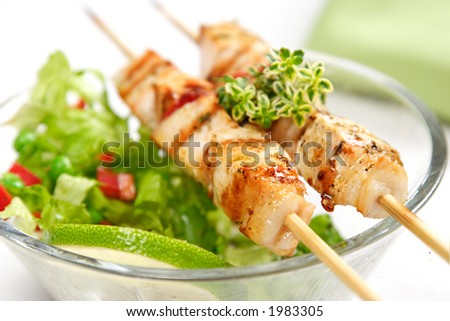 pork (or chicken) on a grill spit with salad and a slice of lime and lemon-thyme as garnish