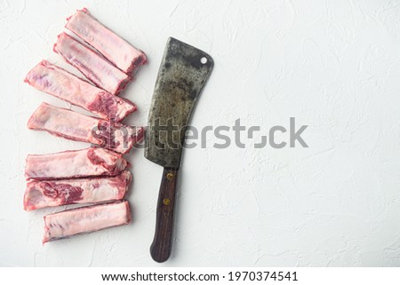 Pork rib set, and old butcher cleaver knife, on white stone background, top view flat lay, with copy space for text Stock photo ©