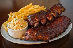 Pork ribs back with french fries and coleslaw salad on the side. Shallow depth of field.