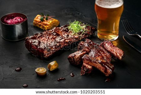 Pork ribs in barbecue sauce and a glass of beer on a black slate dish. A great snack to beer on a dark stone background. Top view with copy space #1020203551