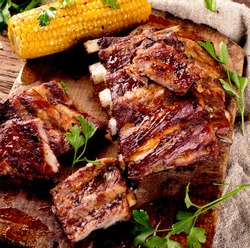 Pork ribs with corn on a wooden board. American food. View from above.