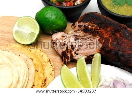 Pork roast cooked to make Mexican carnitas with fresh tortilla's' chunky tomato salsa and salsa verde and sliced limes - stock photo