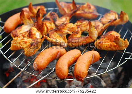 pork sausages  and chicken wings on smoking grill in the garden