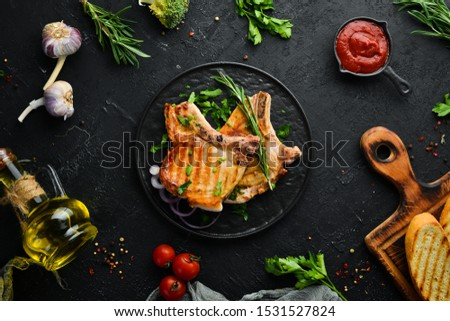 Pork steak on a bone with rosemary and greens in a black plate. Top view. Free copy space. #1531527824