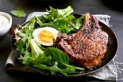 Pork steak with green salad. Close up view.