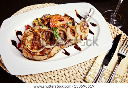 Pork steak with onion, tomatos and rosemary on white plate