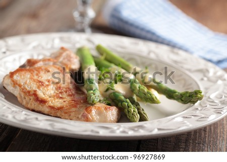 Pork steak with steamed asparagus under cheese sauce. Shallow DOF