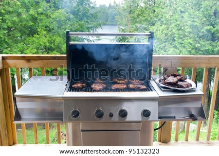 Pork steaks on gas grill in cottage