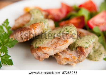 Pork Tenderloin with Cilantro Pesto Served Over Arugula and Tomato Salad