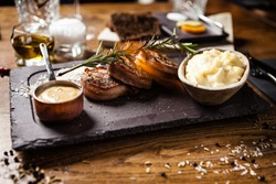 Pork tenderloin with mashed potatos, bacon and mustard sauce with branch of smoking rosemary. Delicious healthy traditional grilled meat food served for lunch in modern cuisine gourmet restaurant