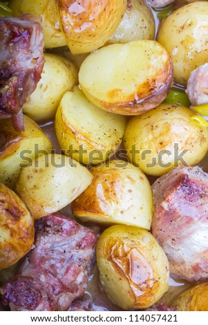 Pork with onion accompanied by garlic roasted potatoes