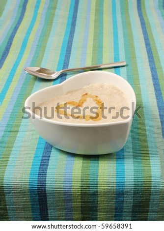 porridge in a heart shaped bowl on a stripey canvas background with a silver spoon