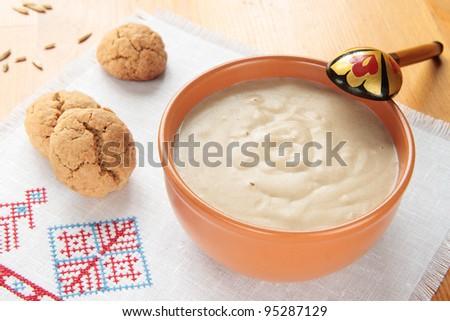 Porridge of oatmeal in a ceramic bowl and oat cookies