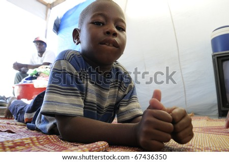 PORT-AU-PRINCE - AUGUST 28: A Haitian  kid relaxing inside his tent-most of the kids inside the tent cities have no scope of getting formal education,  in Port-Au-Prince, Haiti on August 28, 2010.