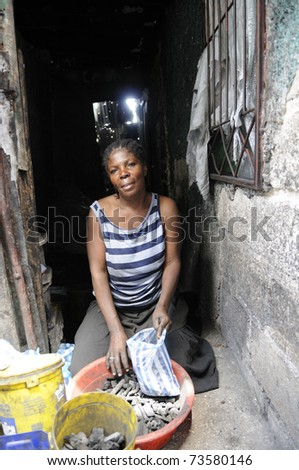 PORT-AU-PRINCE - AUGUST 25: A woman selling coal in her shack after the earthquake destroyed her house just to survive in Cite Soleil, in Port-Au-Prince, Haiti on August 25, 2010.
