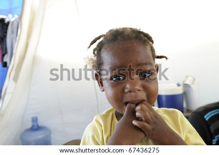 PORT-AU-PRINCE - AUGUST 28:   An unidentified  Haitian kid  biting her fingers out of starvation in , Port-Au-Prince, Haiti on August 28, 2010.
