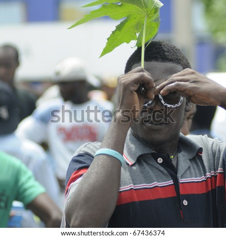 PORT-AU-PRINCE - SEPTEMBER 1:  A Haitian teenager hiding his face from the photographer during a rally , in Port-Au-Prince, Haiti on September 1, 2010.