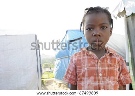 PORT-AU-PRINCE - SEPTEMBER 2:   An unidentified Haitian kid  posing for the camera  on the walkway of her tent city,in Port-Au-Prince, Haiti on September 2, 2010.