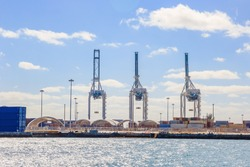 Port cargo crane and container over blue sky background, ready for shipment