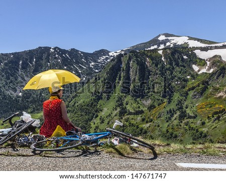 PORT DE PAILHERES,FRANCE- JUL 6: Unidentified woman with a yellow umbrella admires the landscape at the Col de Pailheres during the stage 8 of edition 100 of Le Tour de France on July 6 2013.