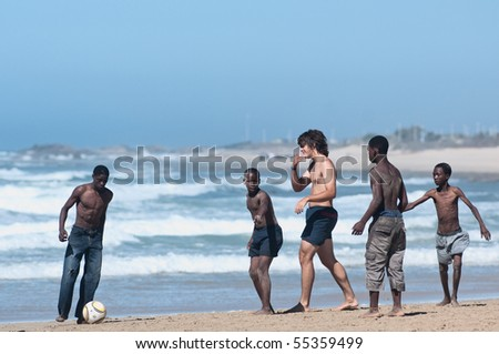 PORT ELIZABETH - MAY 02: black and white boys play soccer in the humewood beach. the country in june 2010 will host the world cup of soccer, may 02 2010 in Porth Elizabet, South Africa