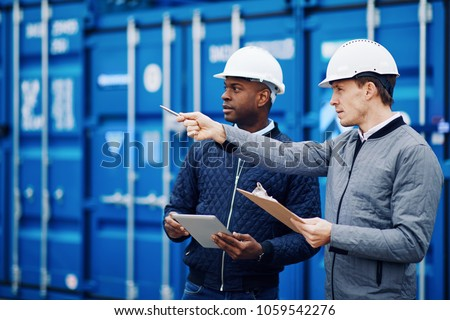 Port manager and a colleague tracking inventory while standing together by freight containers on a large commercial shipping dock