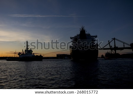 Port of Amsterdam, Noord-Holland/Netherlands - April 05-04-2015 - Tugboat Triton is connected to motor vessel Grand Ann Belle and assisting with departure. Photo taken during sunset.