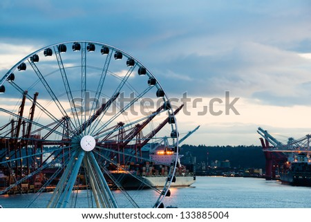 Port of Seattle with sea going cargo ships and Great Ferris Wheel at twilight. Copy space.