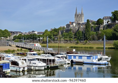 Port on the Maine river of Angers and the cathedral Saint Maurice at the top of hill in the background. Angers is a commune in the Maine-et-Loire department in western France