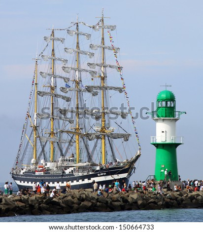 "PORT WARNEMUENDE, GERMANY - AUGUST 10 Old russian Sailing ship ""Kruzenstern&q uot; passing the light beacon on August 10, 2013 in the scope of the 23. Hanse-Sail in Rostock, Mecklenburg-Vorpomm ern, Germany - stock photo"