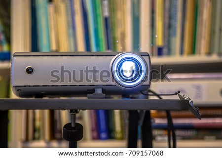 Photo of  Portable beamer projector working on an office during presentation of bussines results
