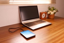 Portable external hard drive USB3.0 connect to laptop computer on desk, Data transfer or backup personal files concept
